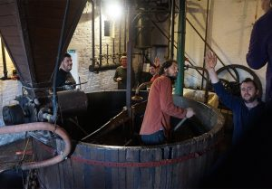Local lads empty the mash tun at Brasserie à Vapeur, Pipaix, Belgium
